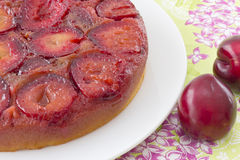 Plum cake. Upside down plum cake on white plate, with whole plums on the side Royalty Free Stock Photo