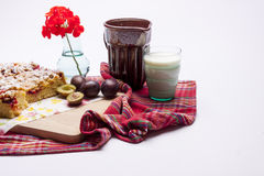 Plum cake and cup of milk on white. Royalty Free Stock Photos