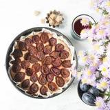 Plum cake with tea mug, fresh plums, brown sugar and flowe. Whole plum cake with tea mug, fresh plums, brown sugar and flowers. Top view Stock Images