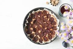 Plum cake with tea mug, fresh plums, brown sugar and flowe. Whole plum cake with tea mug, fresh plums, brown sugar and flowers. Top view Stock Photo