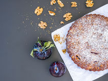 Plum cake with walnuts on white paper over a black background Royalty Free Stock Photos