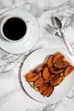 Plum cakes and coffee. A piece of plum cakes on a white plate in addition a cup of black coffee. Spoons and pastry fork lie handy Royalty Free Stock Photography