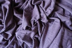 Plum colored simple stockinette fabric in folds. Plum colored simple stockinette fabric in soft folds Royalty Free Stock Image