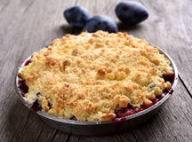 Plum crumb pie. In pan on wooden background royalty free stock photos