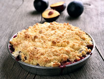 Plum crumb tart in pan. On wooden background royalty free stock images