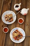 Plum crumble and black tea. On wooden background Stock Images
