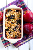 Plum crumble with oat and raisin topping Royalty Free Stock Photography
