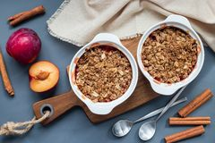 Plum crumble pie or plum crisp with oats and spices, in baking d stock photography