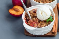 Plum crumble pie or plum crisp with oats and spices, served with stock photos