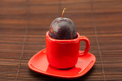 Plum  in a cup and saucer Royalty Free Stock Image