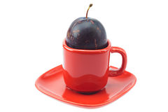 Plum in a cup and saucer Stock Photo