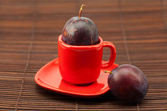 Plum  in a cup and saucer on a bamboo mat Royalty Free Stock Image