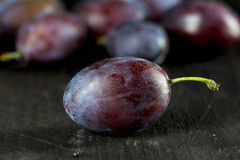 Plum on dark wood, closeup against blurred plums in the backgrou Stock Photos
