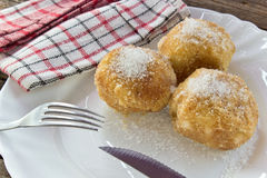 Plum dumplings on plate with fork on wooden table Royalty Free Stock Image