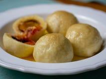 Plum dumplings Zwetschgenknödel on a white plate stock photo