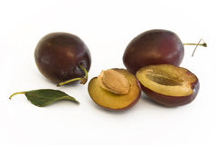 Plum fruits with halve. Plums with halve and pip, green leaf lying besides royalty free stock image