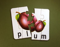 Plum fruits in puzzle. Board with green background royalty free stock photo