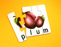 Plum fruits in puzzle. Board with yellow background stock photos