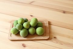 Plum fruits on wooden table. Green plum fruits on wooden table royalty free stock images