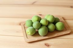 Plum fruits on wooden table. Green plum fruits on wooden table stock photography