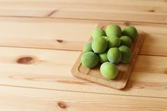 Plum fruits on wooden table. Green plum fruits on wooden table royalty free stock image
