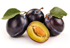 Plum and a half and leaves Stock Images