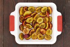 Plum halves in white baking dish. Overhead view royalty free stock image