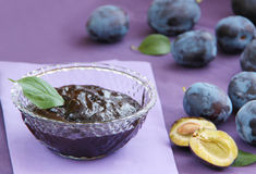 Plum jam in a glass bowl. Fruity marmalade and fresh plums. Close up view. Royalty Free Stock Photos