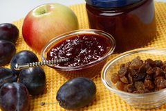 Plum jam and raisins in glass bowl. On table Stock Photo