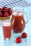 Plum juice in a glass and pitcher, plums in a wicker basket Royalty Free Stock Photos