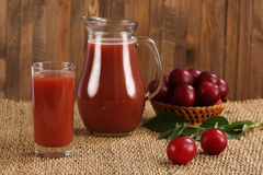 Plum juice in a glass and pitcher, plums in a wicker basket Royalty Free Stock Photography