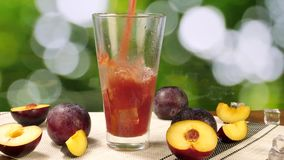 Plum Juice Poured into Glass with Ice Cubes