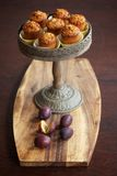 Plum muffins on cake stand on wooden board with plums Royalty Free Stock Images
