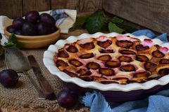 Plum pie in white ceramic form on a wooden background. Homemade baking. Stock Photo
