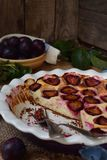 Plum pie in white ceramic form on a wooden background. Homemade baking. Healthy pastries. Vegetarian food. Rustic photo. Copy spac royalty free stock photo
