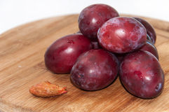 Plum pit and fresh plums on the board Stock Photos