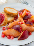 Plum and pomegranate seeds on a plate Royalty Free Stock Photo