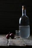 Plum rakiya, Romanian tuica. Plums Schlivowitz, Romanian tuica made of plums, wooden background, Balkan drink stock photos