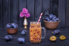 Plum smoothies and raw plums on black wooden background. Close up Stock Photography