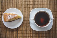 Plum sponge cake over a cup of hot tea on a straw bedding. royalty free stock images