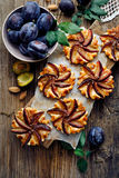 Plum tarts with cinnamon on a wooden table, delicious dessert with puff pastry and fruits stock image