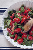 Plum tomato and spinach salad. In white bowl on rustic table napkin with wooden spoon Royalty Free Stock Images