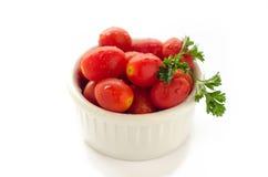 Plum tomatoes in white bowl. Fresh plum tomatoes in white bowl and isolated white background Stock Image