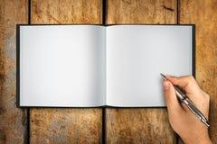 Pluma abierta de la escritura de la mano del libro en blanco