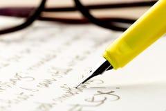 Pluma amarilla que escribe una letra, vidrios detrás foto de archivo