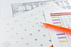 Pluma anaranjada colocada en plan de la reunión en calendario Imágenes de archivo libres de regalías