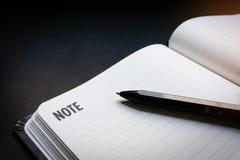 Pluma ascendente cercana colocada en la línea en blanco abierta cuaderno con el fondo negro del escritorio en tono de iluminación imagenes de archivo