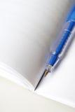 Pluma azul en el libro abierto del blanco Imágenes de archivo libres de regalías