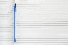 Pluma azul en un cuaderno fotos de archivo libres de regalías