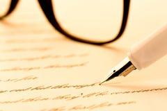 Pluma blanca que escribe una letra, vidrios fotos de archivo